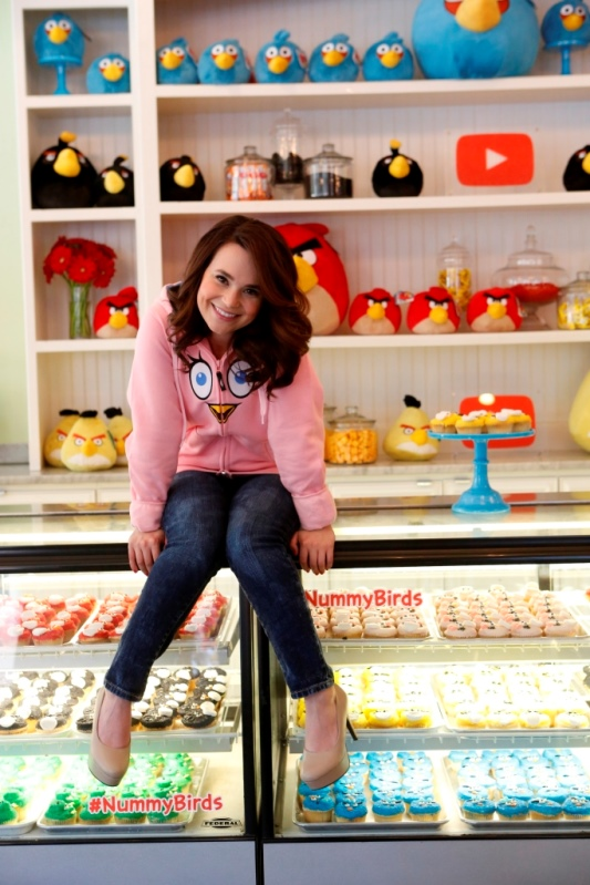 Rosanna Pansino sitting on the cupcake display at The Little Cupcake Bakeshop Youtube Angry Birds Event